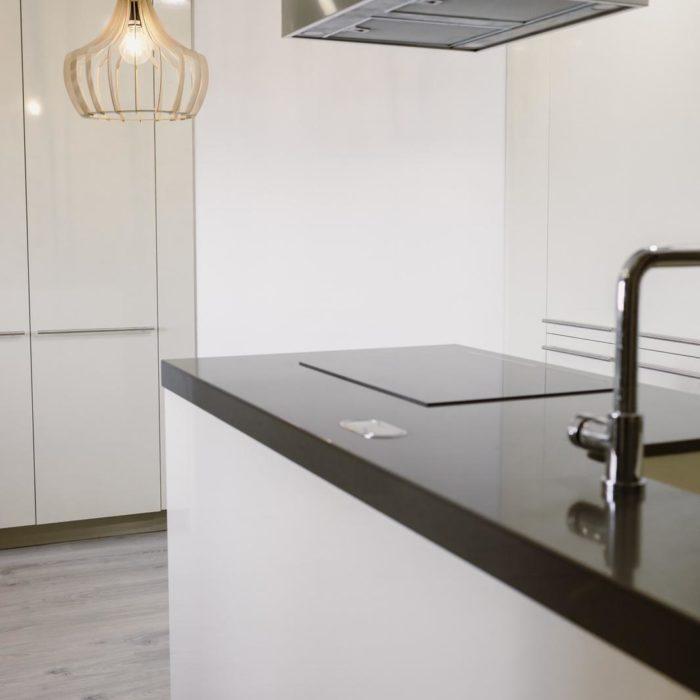 cocina armarios blancos con encimera negra