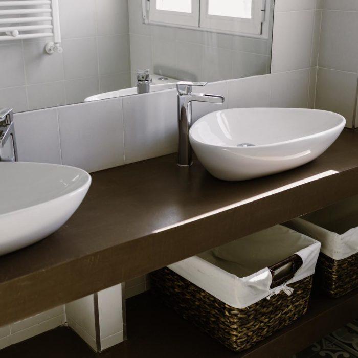 baño con lavabo doble y encimera de madera