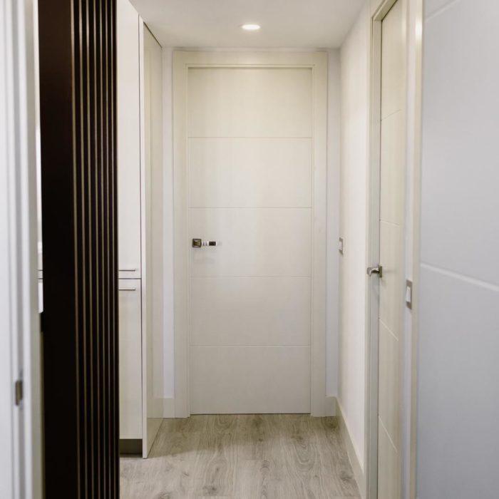 piso reformado entrada con puerta blanca